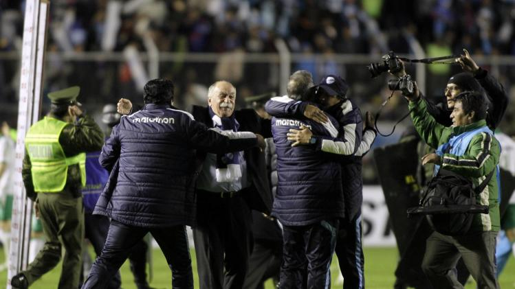 Xavier Axcargorta, coach of Bolivia's Bolivar, celebrates with his assistants as they advanced to the next round of the Copa Libertadores after their draw with Mexico's Leon, in La Paz