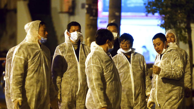 Workers in protective clothing chat during a culling operation as authorities detected the new bird flu strain in pigeons being sold for meat at a wholesale market in Shanghai on Friday April 5, 2013. China announced a sixth death from a new bird flu strain Friday, while authorities carried out the slaughter of all poultry at a Shanghai market where the virus was detected in pigeons being sold for meat. (AP Photo) CHINA OUT