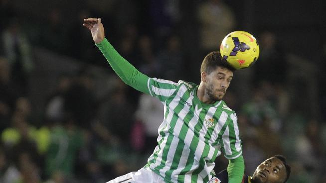 Barcelona's Alexandre Songl, right, and Betis's Didac Vila, top, fight for the ball during their La Liga soccer match at the Benito Villamarin stadium, in Seville, Spain on Sunday, Nov 10, 2013
