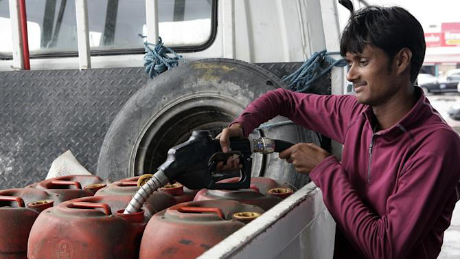 In this Saturday, Dec. 1, 2012 photo, a man fills gasoline in plastic containers at a gas station in Doha, Qatar. The host of the current U.N. climate talks, Qatar, is among dozens of nations that keep gas prices low through subsidies that exceeded $500 billion globally last year. (AP Photo/Osama Faisal)