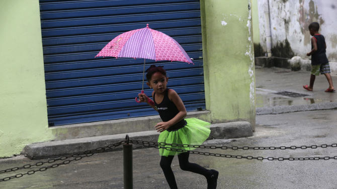 A young dancer from the Afro Reggae center covers herself from the rain after performing for members of London's Royal Opera House in the Vigario Geral slum in Rio de Janeiro, Brazil, Saturday, March 2, 2013. This past week Royal Ballet dancers shared their knowledge and advice with promising artists during an education symposium between the company and the cultural arts center Afro Reggae. (AP Photo/Silvia Izquierdo)