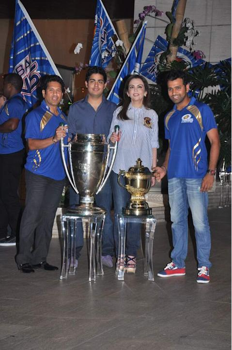 Sachin Tendulkar, Akash Ambani, Nita Ambani and Mumbai Indians skipper Rohit Sharma pose with the CLT20 and IPL trophies