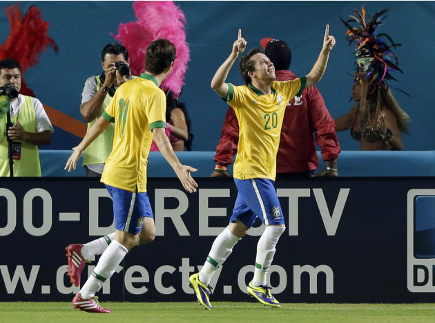 Brazil forward Bernard (20) celebrates his goal with midfielder Oscar (11) during the first half of an international friendly soccer game against Honduras, Saturday, Nov. 16, 2013, in Miami Gardens, F