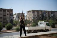 A rebel fighter fires his AK-47 rifle towards a Syrian helicopter in Aleppo's Hanano district. The Syrian army on Monday sent shells slamming into rebel strongholds in Damascus province, where more than 45 people, including 36 civilians, have been killed in the past 48 hours, a watchdog said