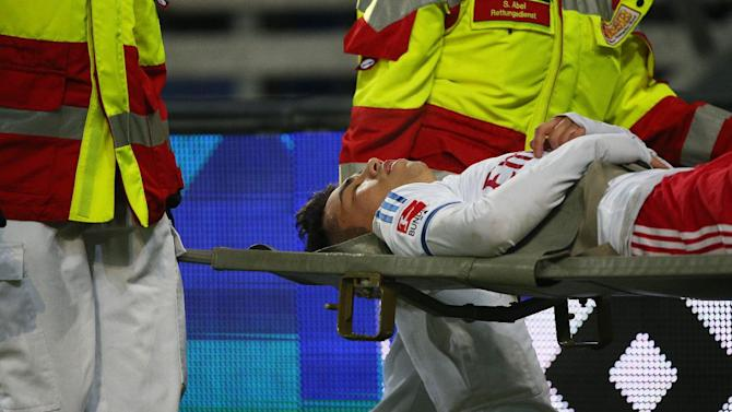 Hamburg's Lam  Zhi Gin is carried on a stretcher during the German Bundesliga soccer match between Hamburger SV and Schalke 04, in Hamburg, Germany Sunday Jan. 26, 2014