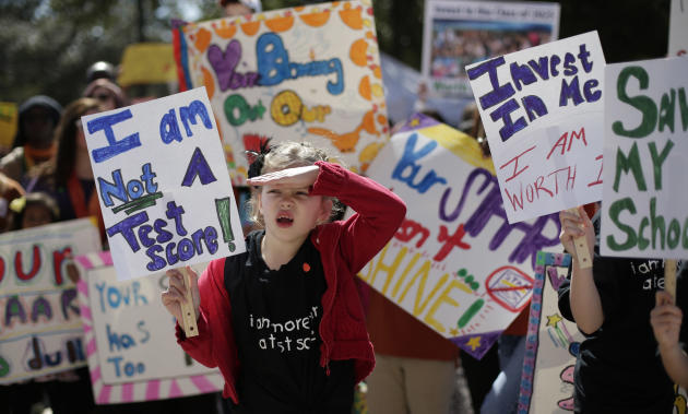 FILE - In this Feb. 23, 2013 file photo, Cate Foughty, 6, of Frisco, Texas, takes part in a rally for Texas public schools at the state Capitol, in Austin, Texas. Ninth-graders who were barely a month
