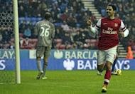 Arsenal's midfielder Mikel Arteta (R) celebrates scoring the opening goal on December 22, 2012. Arsenal climbed to third place in the Premier League as Arteta's second half penalty sealed a 1-0 win over Wigan at the DW Stadium