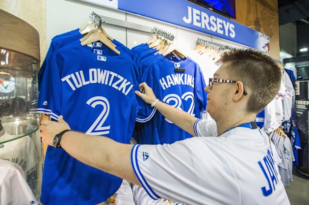 Toronto Blue Jays store employee Nico Canavo puts a Troy Tulowitzki jersey up in the store next to a LaTroy Hawkins jersey in Toronto, Tuesday July 28, 2015. The Colorado Rockies and Toronto Blue Jays