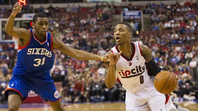 Portland Trail Blazers' Damian Lillard, right, drives to the basket with Philadelphia 76ers' Hollis Thompson, left, defending during the first half of an NBA basketball game on Saturday, Dec. 14, 2013, in Philadelphia. The Trail Blazers won139-105