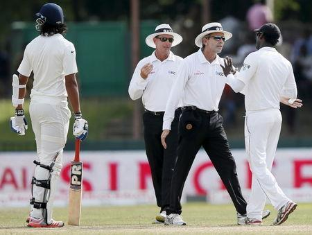 Umpire Llong talks to Sri Lanka's captain Mathews after an argument between India's Sharma and Sri Lanka's bowler Prasad during the fourth day of their third and final test cricket match i