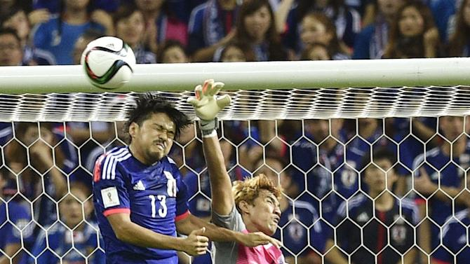 Cambodia's goalkeeper Sou Yaty, right, jumps to stop a header by Japan's Shinzo Koroki (13) during their second round soccer match of regional qualifiers for the 2018 World Cup in Saitama, north of Tokyo Thursday, Sept. 3, 2015. Japan defeated Cambodia 3-0 to secure its first win of World Cup qualifying. (Tsuyoshi Ueda/Kyodo News via AP) JAPAN OUT, MANDATORY CREDIT