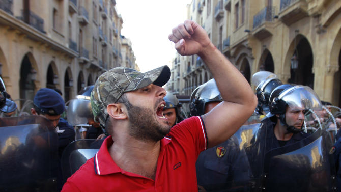 A civil society protester chant slogans against Lebanese lawmakers during a demonstration protesting the extension of parliament's mandate, near Parliament in Beirut, Lebanon, Friday, June 21, 2013. Lebanon's parliament on May 29 extended its term by a year and a half, skipping scheduled elections because of the country's deteriorating security linked to the civil war next door in Syria. (AP Photo/Bilal Hussein)