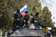 Pro-Russian supporters sit on top of a Ukrainian APC after breaking into the territory of the naval headquarters in Sevastopol, March 19, 2014. REUTERS/Baz Ratner