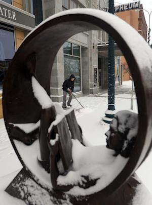 Micki DeCurtins shovels freshly fallen snow  outside of the Orpheum Theater off of Phillips Ave. in downtown Sioux Falls, S.D. on Thursday, Dec.27, 2012. (AP Photo/The Argus Leader, Jay Pickthorn)  NO SALES