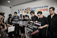Survivors and relatives of eight Hong Kong tourists who were killed exactly two years ago in a 2010 Philippine bus hostage fiasco in Manila gather outside the Philippines consulate in Hong Kong to demand an apology