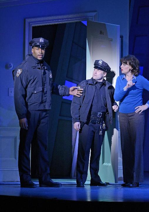 "This image released by ABC shows former NFL player Michael Strahan, left, portraying a police officer on stage with Lee A. Wilkins, center, and Beth Leavel during the matinee show of the musical ""Elf,"