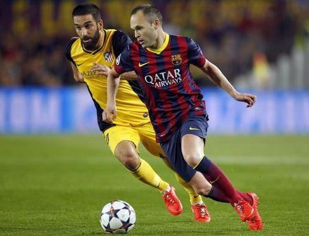 Barcelona's Iniesta and Atletico Madrid's Turan challenge for teh ball during their Champions League quarter-final first leg soccer match in Barcelona