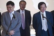 Co-chairman and Managing Directors of Sun Hung Kai Properties Raymond Kwok (L) and Thomas Kwok (R) react as they speak to the press after they were charged for corruption in Hong Kong. Two of Hong Kong's richest tycoons and a former senior official were charged with corruption in the biggest graft scandal the regional banking hub has seen