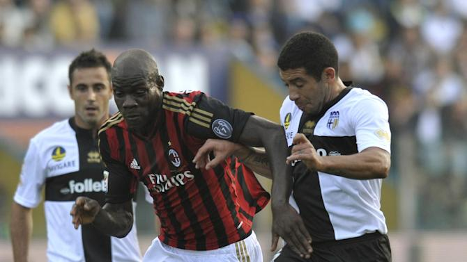 Parma's Walter Gargano of Uruguay, right, vies for the ball with AC Milan's Mario Balotelli, during their Serie A soccer match at Parma's Tardini stadium, Italy, Sunday, Oct. 27, 2013