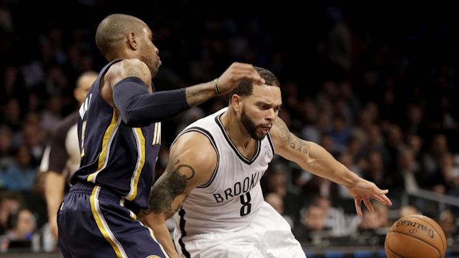 Brooklyn Nets' Deron Williams, right, loses the ball while being guarded by Indiana Pacers' C.J. Watson during the second half of an NBA basketball game Monday, Dec. 23, 2013 in New York. The Pacers defeated the Nets 103-86