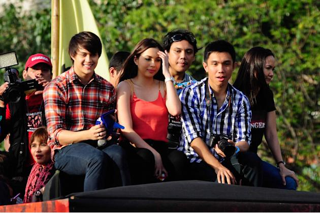 """Enrique Gil and Julia Montes are seen at the float of their MMFF 2012 entry """"The Strangers"""" during the 2012 Metro Manila Film Festival Parade of Stars on 23 December 2012. (Angela Galia/NPPA Images)"""