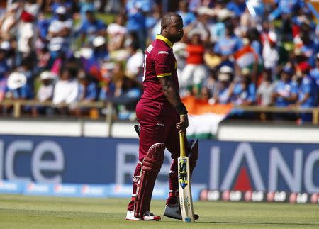West Indies batsman Dwayne Smith walks off the field after he was caught out by India's wicketkeeper MS Dhoni during their Cricket World Cup match in Perth