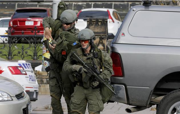 Armed RCMP officers approach Parliament Hilll following a shooting incident in Ottawa