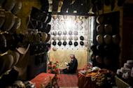 """An elderly Chinese Muslim Uighur man prays at his hat shop in Kashgar, in farwest China's Xinjiang region, at the end of Ramadan in 2011. Beijing rejected Thursday accusations from the United States that it was curbing religious freedoms in its Tibetan regions and urged Washington to cast off its """"prejudiced"""" views of China"""