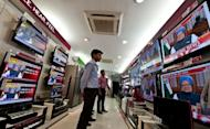 Bystanders watch television screens with Indian Prime Minister Manmohan Singh as he addresses the nation in New Delhi. India's Prime Minister Manmohan Singh mounted a defiant defence Friday of reforms that resulted in the loss of his government's majority, saying he had to act to bolster growth and restore confidence