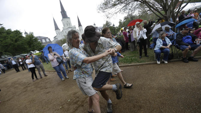 Gretchen Newman and Steven Yesner, of Albequerque, dance to live music on the first day of the annual French Quarter Festival in New Orleans, Thursday, April 11, 2013.  French Quarter Festival, which turns 30 this year, runs through Sunday and showcases Louisiana food and music on stages strung throughout the historic neighborhood, including Jackson Square, the French Market, along narrow streets and on the Mississippi riverfront. The lineup includes Irma Thomas, trumpeter Kermit Ruffins, Cajun fiddler Amanda Shaw, the Dirty Dozen Brass Band and about 250 other acts. (AP Photo/Gerald Herbert)