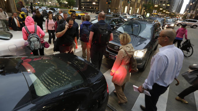 Pedestrian and auto traffic snarl Wednesday, June 12, 2013, in Chicago as commuters race to avoid an unusually massive line of storms packing hail, lightning and tree-toppling winds that have been forecast for evening rush hour. (AP Photo/M. Spencer Green)