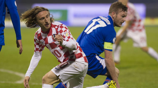 ZAGREB, Nov. 20, 2013 (Xinhua/IANS) -- Luka Modric (L) of team Croatia vies with Aron Gunnarsson of team Iceland during their 2014 World Cup qualifying second leg playoff soccer match in Zagreb, Croatia, on Nov. 19, 2013. Coatia won 2-0 in total to be qualified for the final stage of the 2014 World Cup. (Xinhua/Miso Lisanin)