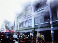 This picture, taken by a local resident in Fukuyama on May 13, shows firefighters and rescue workers fighting a fire at a four-story hotel. Six people have been killed when a fire swept through their hotel in southwestern Japan, the local police and fire department said