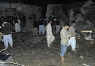 Local residents search for blast victims at the site of a bomb attack in Quetta on January 10, 2013. At the snooker club the first suicide bomber struck inside the building, then 10 minutes later an attacker in a car outside blew himself up as police, media workers and rescue teams rushed to the site