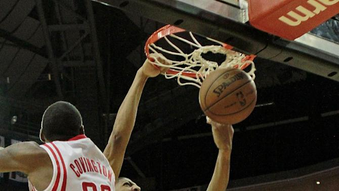 New Orleans Pelicans forward Anthony Davis slam dunks the ball over Houston Rockets forward Robert Covington, 33, and center Donatas Motiejunas during the second half of a preseason NBA basketball game in Houston, Saturday, Oct. 5, 2013. The Pelicans won the game 116-115
