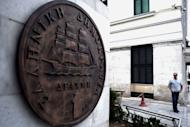 A man stands near a monument featuring a replica of the last edition of the Greek currency, the drachma. Greece's president called Monday for talks on a technocrat government, seeking to resolve the crisis over a tough EU-IMF debt bailout which risks forcing the country into new elections and out of the eurozone