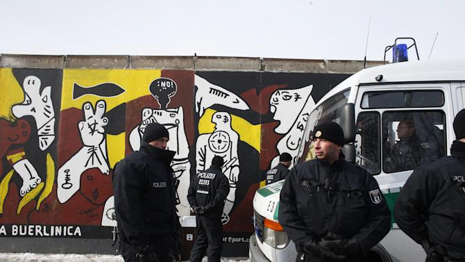 Police officers guard in front of a remaining part of the Berlin Wall in Berlin on Wednesday, March 27, 2013. Work crews backed by about 250 police have removed portions of the Berlin Wall known as the East Side Gallery to make way for an upscale building project, despite demands by protesters that the site be preserved. Plans to remove part of the 1.3-kilometer (3/4-mile) stretch of wall sparked protests that developers were sacrificing history for profit. (AP Photo/Markus Schreiber)