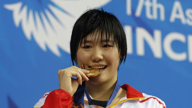 China's Ye bites her gold medal after winning the women's 200m individual medley final swimming competition at the Munhak Park Tae-hwan Aquatics Center during the 17th Asian Games in Incheon