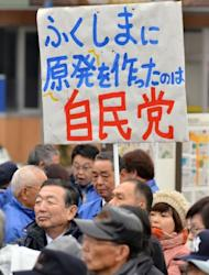 "An anti-nuclear protestor (R in pick coat) displays a placard saying ""Liberal Democratic party (LDP) built nuclear plants in Fukushima"", behind supporters of the LDP near Fukushima, northern Japan on December 4, 2012. The business friendly LDP says only that it will decide over the coming three years whether to restart reactors that were taken offline after the disaster."