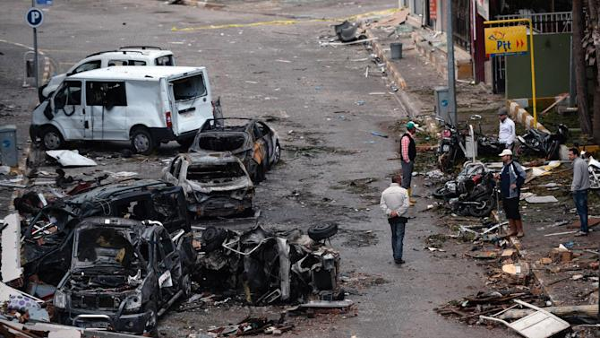 People view the scene at one of the Saturday explosion sites that killed 46 and injured about 50 others, in Reyhanli, near Turkey's border with Syria, Sunday, May 12, 2013.  The bombings on Saturday marked the biggest incident of cross-border violence since the start of Syria's bloody civil war and has the raised fear of Turkey being pulled deeper into the conflict. (AP Photo)