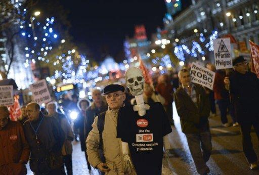 "A demonstrator holds a plastic skeleton with a shirt reading ""Once I had social and labour rights"" during a protest in Madrid on December 17, 2012. Whistles blowing and horns honking, thousands of people demonstrated Monday in Madrid to defend their pensions from the austerity policies of the right-wing government of Mariano Rajoy."