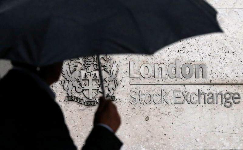 FOTO FILE: Un uomo si nasconde sotto un ombrello mentre passa davanti alla Borsa di Londra