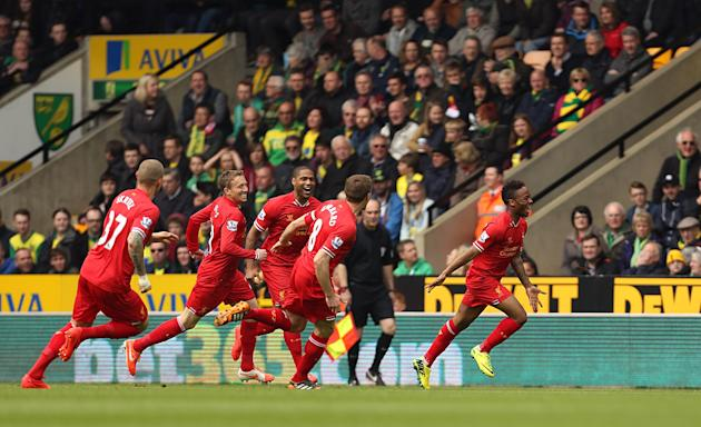 Liverpool's Raheem Sterling, right, celebrates scoring the opening goal during their English Premier League match against Norwich City at Carrow Road, Norwich, eastern England, Sunday April 20, 20