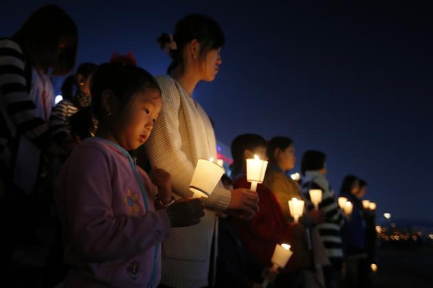 People attend at a candlelight vigil for victims of capsized passenger ship Sewol in Ansan