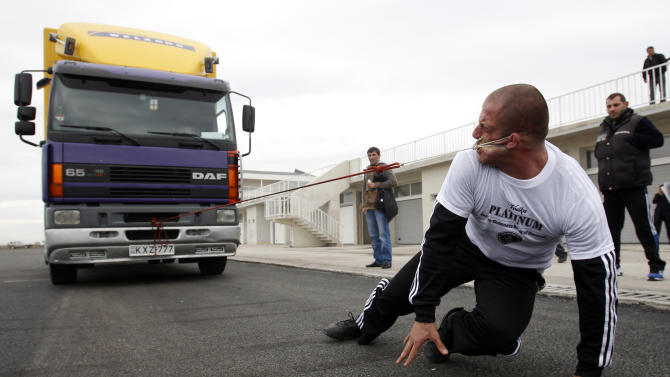 Lasha Pataraia pulls an eight-ton truck with his ear during a test event in Rustavi outside Tbilisi