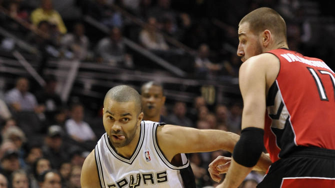 San Antonio Spurs point guard Tony Parker, left, of France, drives around Toronto Raptors center Jonas Valanciunas, of Lithuania, during the first half of an NBA basketball game on Monday, Dec. 23, 2013, in San Antonio
