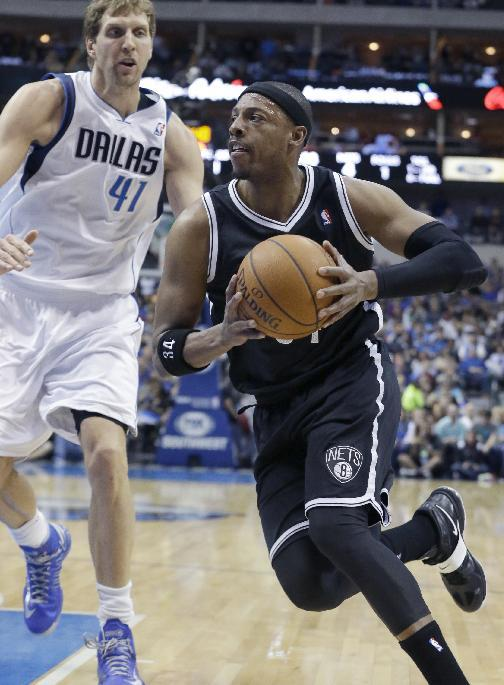 Brooklyn Nets forward Paul Pierce (34) drives past Dallas Mavericks forward Dirk Nowitzki (41) of Germany during the first half of an NBA basketball game Sunday, March 23, 2014, in Dallas