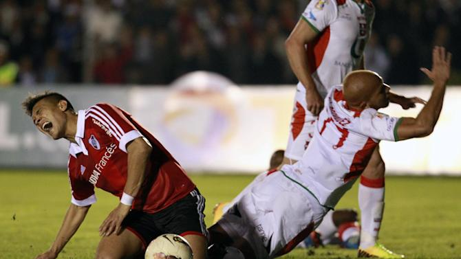 River Plate's Teofilo Gutierrez of Argentina, left, cries out after colliding with Liga Deportiva Universitaria de Loja's Jimmy Bermudez of Ecuador, in their battle for control of the ball during a Copa Sudamericana soccer match  in Loja, Ecuador, Thursday, Sept. 19, 2013