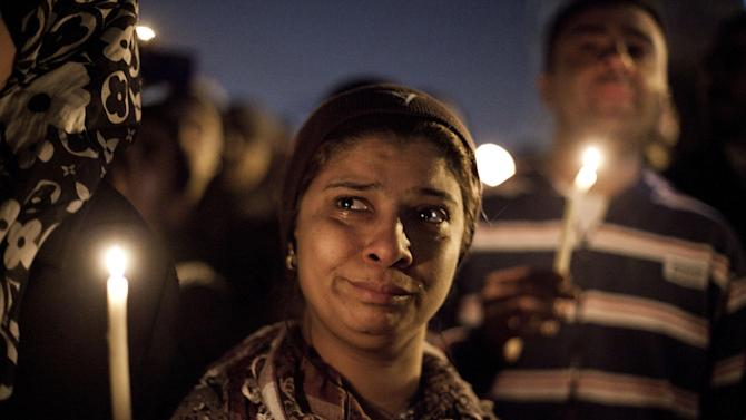 In this Saturday Feb. 2, 2013 photo, demonstrators hold candles in memory of protester Mohammed Qorany, at the spot where he died in clashes, near the presidential palace in Cairo, Egypt. Protesters and rights groups have accused police of using excessive force this past week during a wave of mass demonstrations in cities around the country called by opposition politicians, trying to wrest concessions from Morsi. (AP/Virginie Nguyen Hoang)