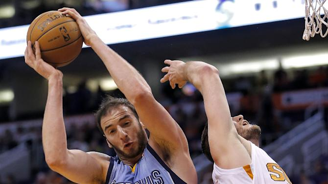 Memphis Grizzlies' Kosta Koufos (41) pulls down a rebound over Phoenix Suns' Miles Plumlee during the first half of an NBA basketball game on Thursday, Jan. 2, 2014, in Phoenix
